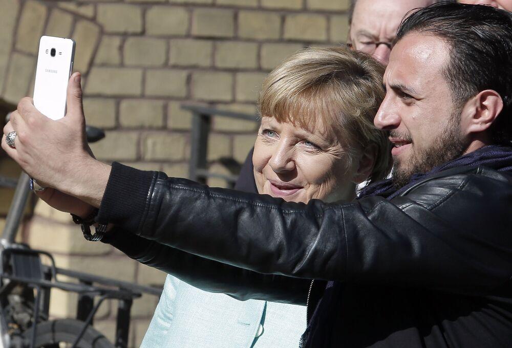 La chancelière allemande Angela Merkel a été photographiée avec un réfugié en visitant un camp à Berlin