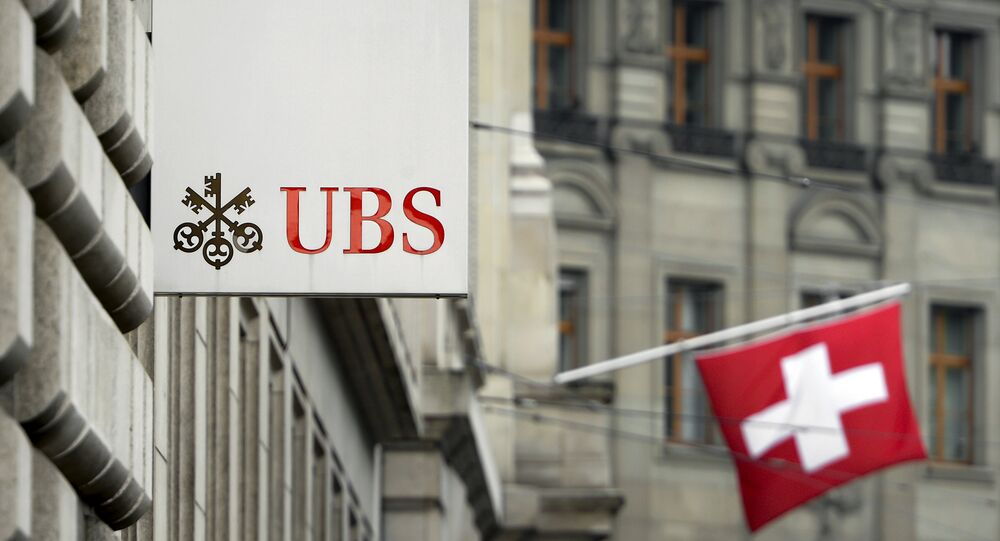 A Swiss flag is seen behind a sign of Swiss bank giant UBS on June 11, 2013 in Basel.