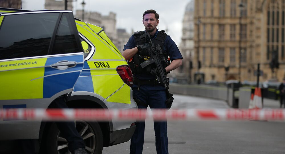 An armed police officer guards inside a police cordon outside the Houses of Parliament in central London on March 22, 2017 during an emergency incident.