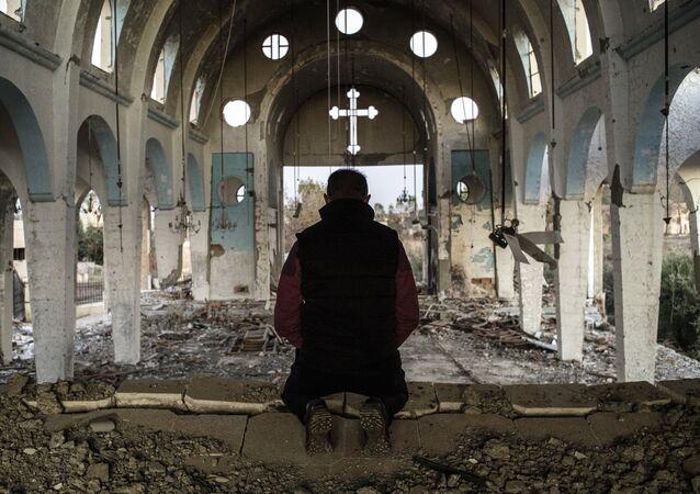 Un résident d'un village de la province d'al-Hasake au nord-est de la Syrie prie dans l'église Saint-Georges détruite par des terroristes d'État islamique.
