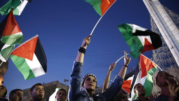Palestinians wave their national flags as they watch a live-screening of president Mahmud Abbas' speech followed by the raising of the Palestinian flag at the United Nations headquarters in New York, on September 30, 2015 in the city of Ramallah - Sputnik France