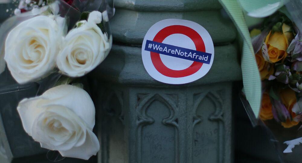 Des bouquets de fleurs et un autocollant montrant le logo du métro de Londres et les mots «Nous n'avons pas peur» en l'honneur des victimes de l'attentat terroriste du 22 mars sont représentés dans le centre de Londres le 23 mars 2017.