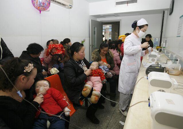 Les patients aident leurs enfants à respirer la médecine liquide atomisée à l'hôpital Xiangyang N ° 1 à Xiangyang, dans la province de Hubei, dans l'est de la Chine