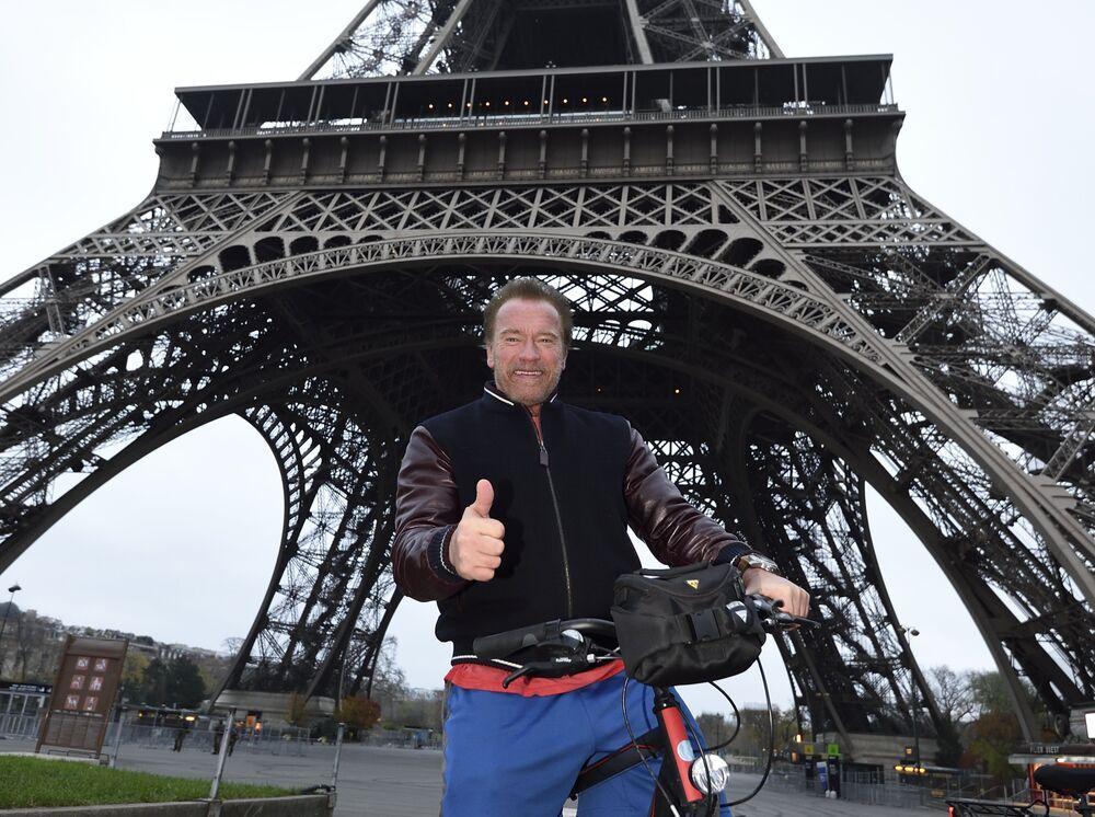 Arnold Schwarzenegger, ex-gouverneur de Californie et acteur américain, pose avec un vélo devant la caméra sous la Tour Eiffel avec les pouces levés après avoir fait le tour de Paris à vélo le 6 décembre 2015.