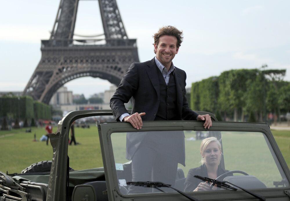 L'acteur américain Bradley Cooper pose dans une voiture devant la Tour Eiffel le 14 juin 2010 pour une séance photo à l'occasion de la sortie du film L'Agence tous risques dans les salles françaises.