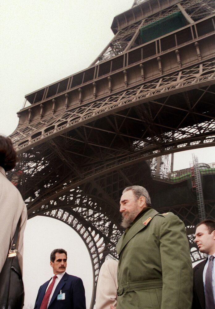 Le Président cubain Fidel Castro (deuxième à droite) marche sous la Tour Eiffel le 14 mars 1995 durant sa visite à Paris. Castro a alors passé quatre jours en France. C'était sa première visite depuis 36 ans.