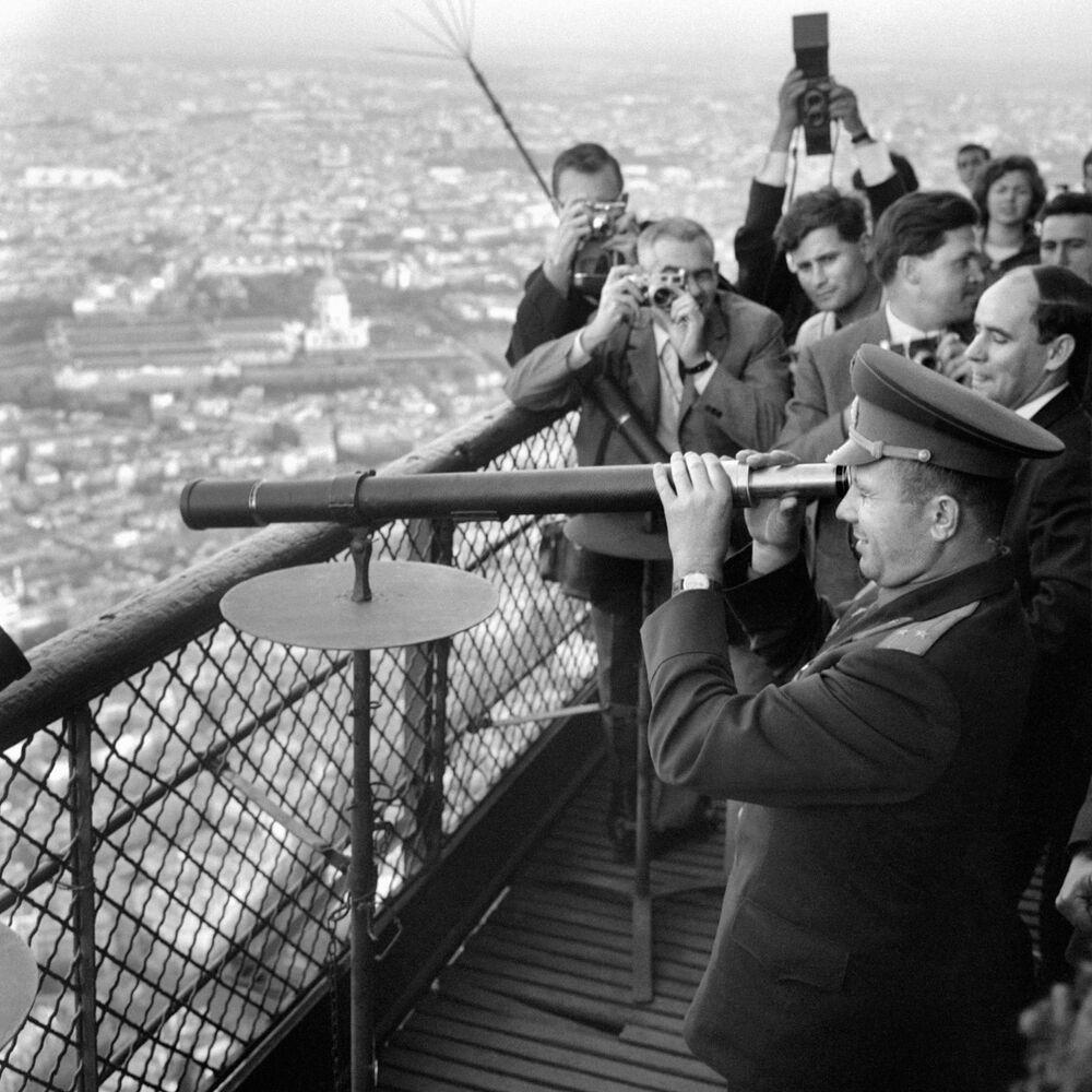Le cosmonaute soviétique Youri Gagarine (à droite) regarde à travers une longue-vue pendant sa visite de la Tour Eiffel le 28 septembre 1963. Youri Gagarine est le premier homme à avoir effectué un vol dans l'espace au cours de la mission Vostok 1 et le premier a avoir été placé en orbite autour de la Terre. Il meurt dans le crash de son Mig 15 lors d'un vol d'entraînement le 27 mars 1968.