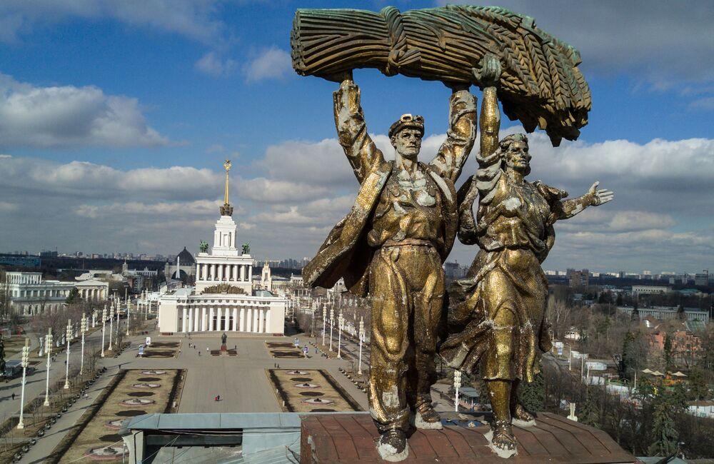 La sculpture « Un tractoriste et une kolkhozienne » sur l'Arc de Triomphe de l'Entrée principale de l'Exposition des réalisations de l'économie nationale à Moscou. Sur le second plan : le pavillon N 1 « Central »