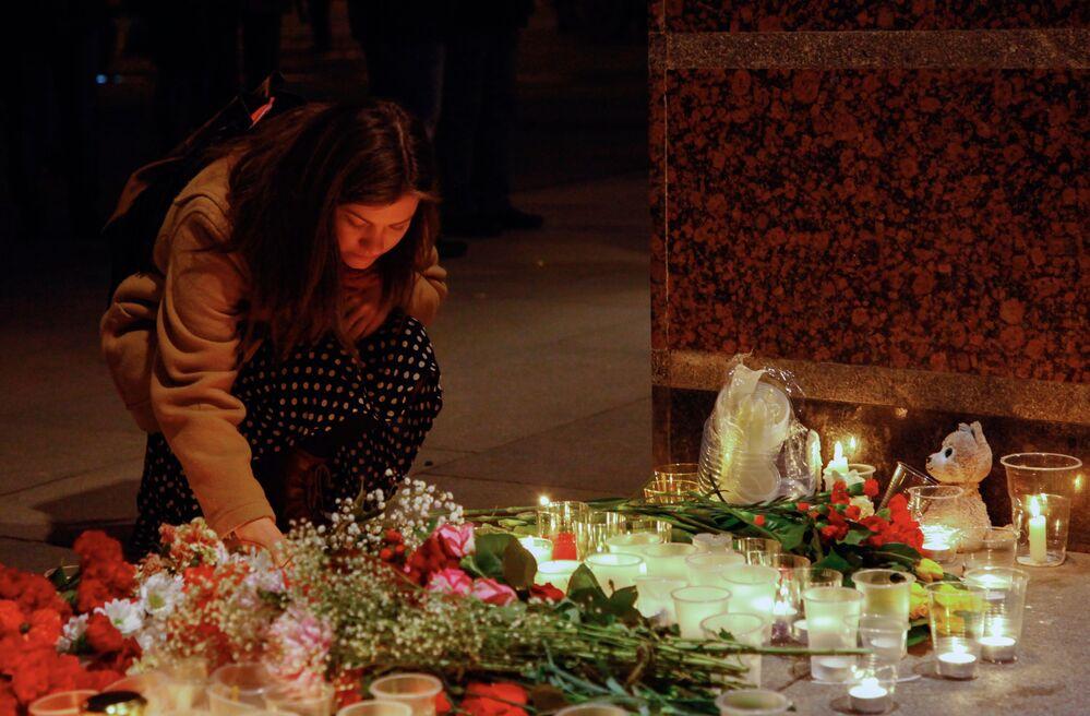 Une jeune femme allume une bougie devant l'entrée du métro Spasskaïa en mémoire des morts du métro de Saint-Pétersbourg