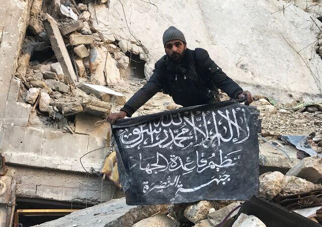 Un soldat syrien démonte le drapeau du Front al-Nosra