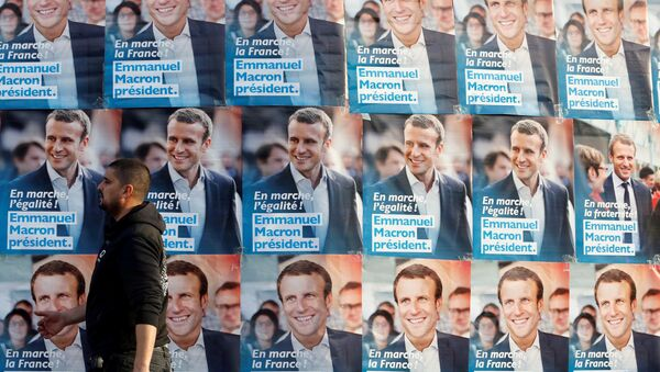 A man walks near posters of Emmanuel Macron, head of the political movement En Marche!, or Onwards!, and candidate for the 2017 presidential elections in France, before Macron's arrival for a meeting in Talence, Southwestern France, March 9, 2017. - Sputnik France