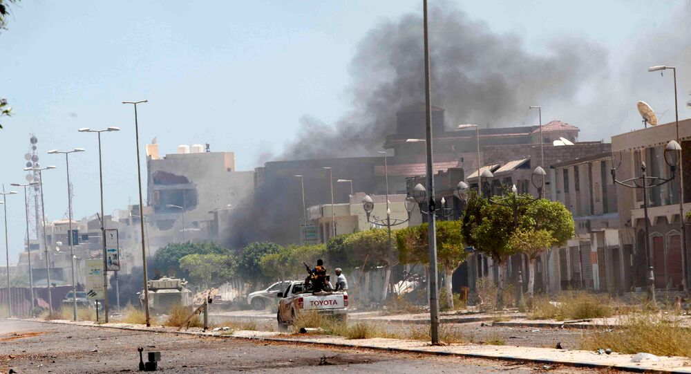 Fighters ride a pickup truck as smoke rises during a battle with Islamic State fighters in neighborhood Number Two in Sirte, Libya