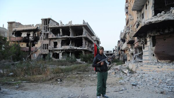 Un combattant civil tient un drapeau libyen preès des bâtiments endommagés à Benghazi, en Libye - Sputnik France