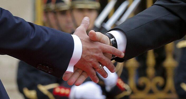 Vladimir Poutine et Emmanuel Macron se serrent la main