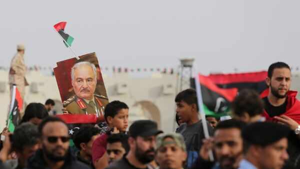 A poster of Libyan military commander Khalifa Haftar is held during celebrations marking the third anniversary of Libyan National Army's ÒDignityÓ operation against Islamists and other opponents, in Benghazi, Libya May 16, 2017. - Sputnik France