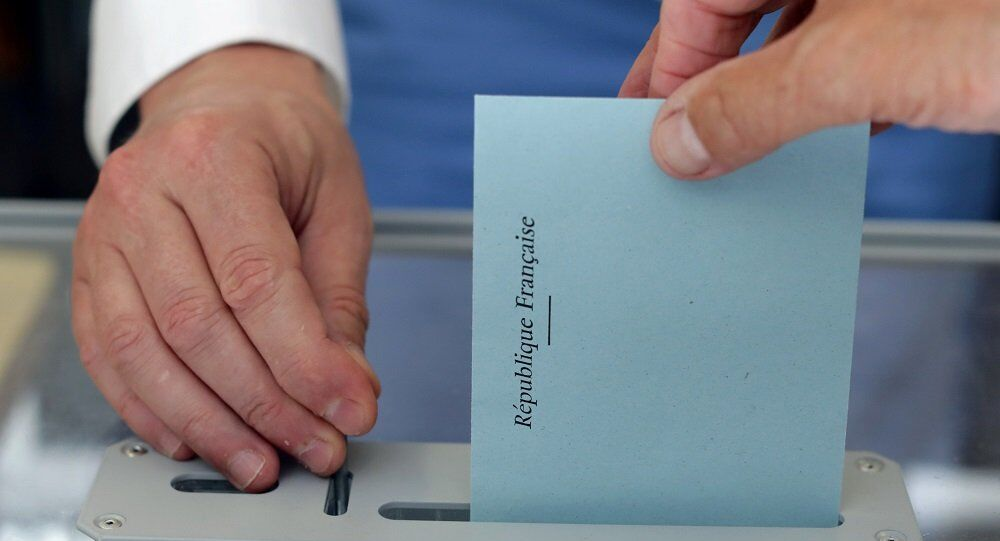 A person casts a ballot in a polling station during the first round of French parliamentary election in Nice