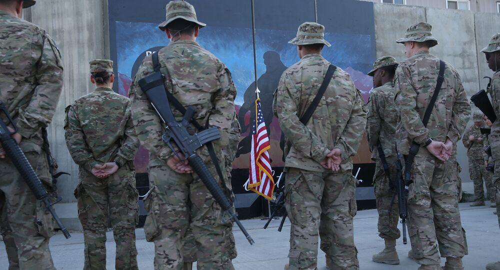 Des membres des services américains se tiennent devant un drapeau américain lors d'une cérémonie à l'occasion du treizième anniversaire des attaques terroristes du 11 septembre 2001 devant le mémorial du World Trade Center à l'aérodrome de Bagram, en Afghanistan, jeudi 11 septembre 2014.
