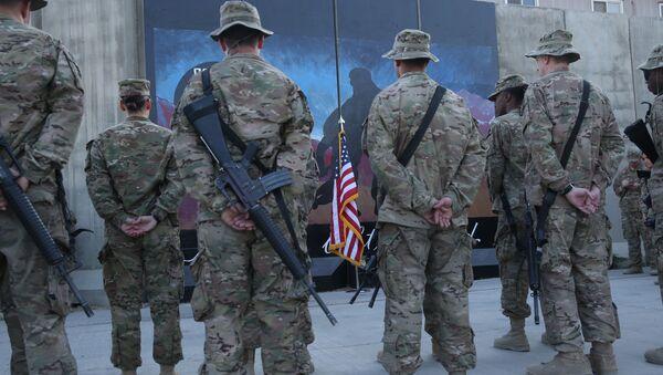 Des membres des services américains se tiennent devant un drapeau américain lors d'une cérémonie à l'occasion du treizième anniversaire des attaques terroristes du 11 septembre 2001 devant le mémorial du World Trade Center à l'aérodrome de Bagram, en Afghanistan, jeudi 11 septembre 2014. - Sputnik France