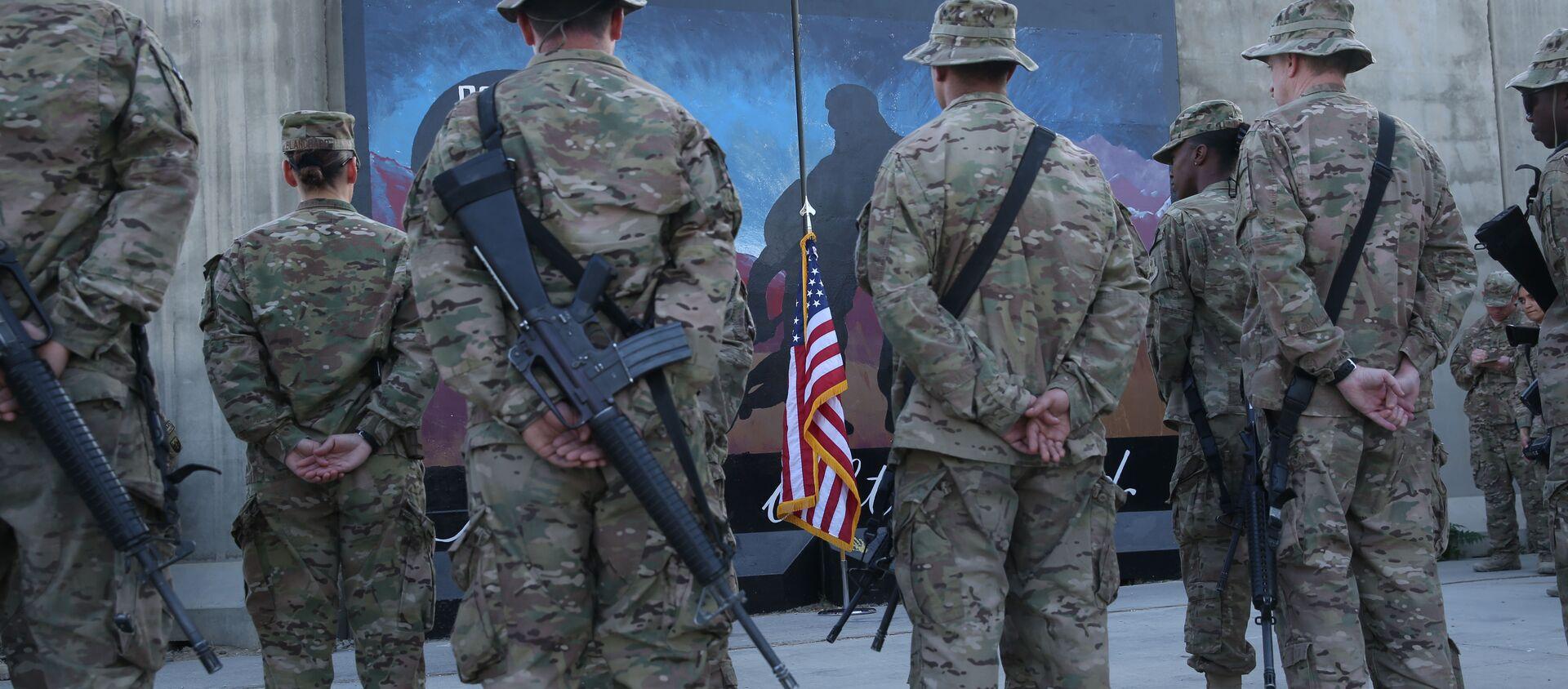 Des membres des services américains se tiennent devant un drapeau américain lors d'une cérémonie à l'occasion du treizième anniversaire des attaques terroristes du 11 septembre 2001 devant le mémorial du World Trade Center à l'aérodrome de Bagram, en Afghanistan, jeudi 11 septembre 2014. - Sputnik France, 1920, 16.08.2021