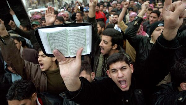 Hundreds of Muslim worshippers gather after Friday prayers hold a copy of the holy Qur'an and shout slogans denouncing Denmark for publishing cartoons of the Prophet Muhammad in 2005, at the revered Abu Hanifa Mosque, Friday, Feb. 3, 2006, in Baghdad, Iraq. - Sputnik France