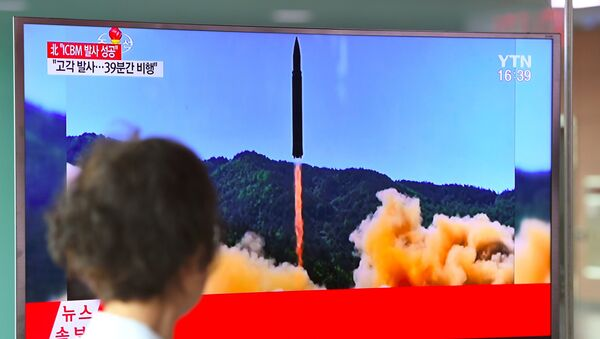 A woman walks past a television screen showing a picture of North Korea's launch of an intercontinental ballistic missile (ICBM), at a railway station in Seoul on July 4, 2017. - Sputnik France