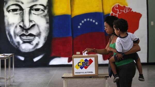A woman holds her infant as she casts her vote in front of a mural of the late Venezuelan President Hugo Chavez at a polling station during the Constituent Assembly election in Caracas, Venezuela, July 30, 2017. - Sputnik France