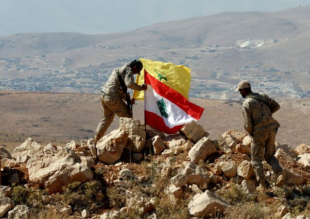 Des combattants du Hezbollah mettent des drapeaux libanais et du Hezbollah à Juroud Arsal, à la frontière syro-libanaise, le 25 juillet 2017.