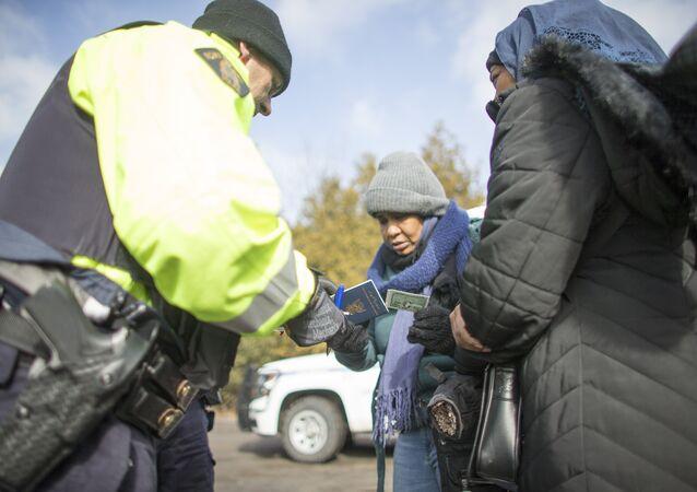 Un agent de la GRC vérifie les documents de deux femmes du Soudan après que les dernières ait franchi illégalement la frontière canado-américaine.