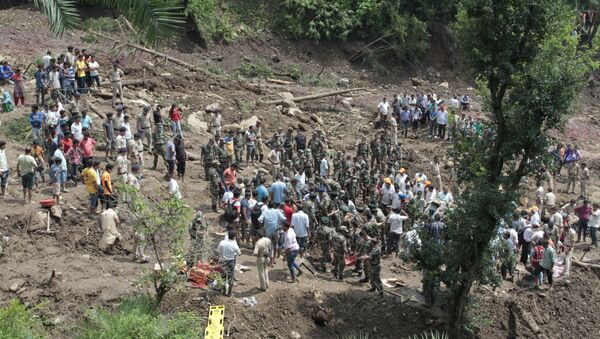 People watch army soldiers and rescue workers recover bodies of landslide victims even as they try to pull out two buses that were covered in mud after a landslide triggered by heavy monsoon rain in Urla village, Himachal Pradesh state, India - Sputnik France