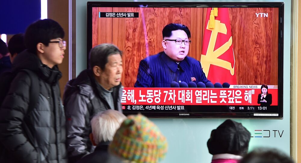 Commuters walk past a television screen showing a broadcast of North Korean leader Kim Jong-Un's New Year speech, at a railroad station in Seoul on January 1, 2016