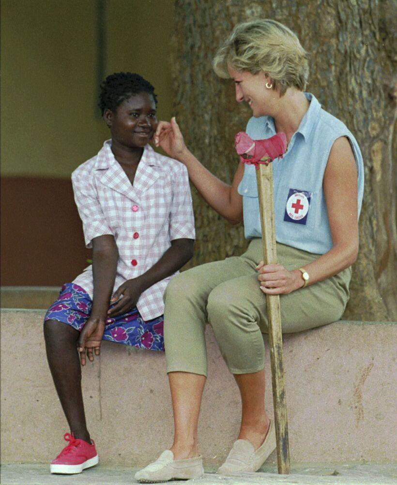 La princesse Diana parle à une petite fille lors de sa visite à Saurimo, en Angola, 1994