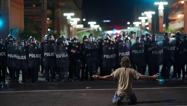 Un manifestant devant les policiers après le rassemblement du président américain Donald Trump à Phoenix, Arizona - Sputnik France