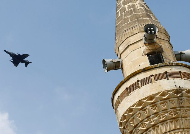 A Turkish Air Force F-4 fighter jet flies over a minaret after it took off from Incirlik air base in Adana, Turkey, August 12, 2015.