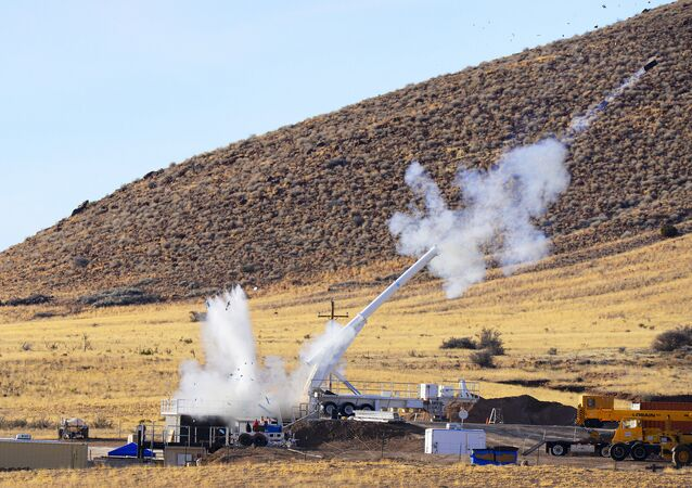A test B61-12 nose assembly fired from Sandia National Laboratories' Davis gun splashes water from an 8-foot-deep pool as a 2,000-pound reaction mass sails into the air from the other end of the gun in a successful impact test at New Mexico Tech's Energetic Materials Research & Testing Center