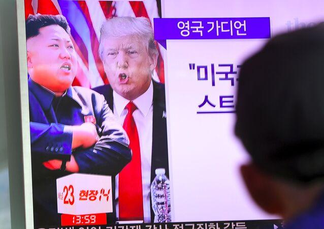 Un homme devant l'écran montrant Kim Jong-un et Donald Trump