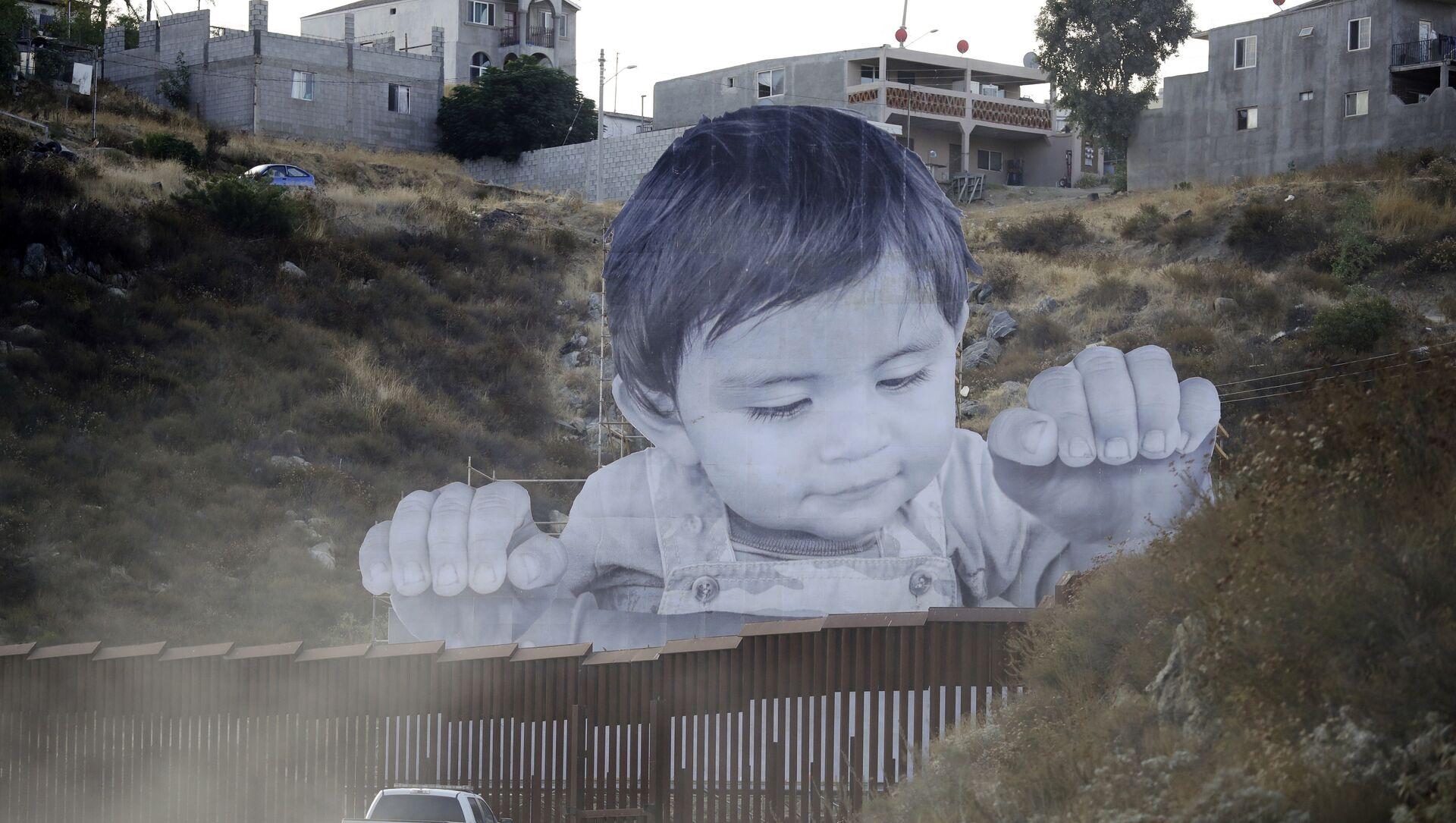 Un garçon géant est apparu sur le mur entre les États-Unis et le Mexique - Sputnik France, 1920, 22.03.2021