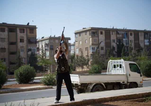 Un rebelle tire d'un fusil d'assaut de type AK-47 contre un hélicoptère de l'armée syrienne