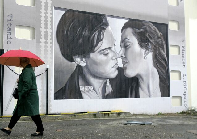 A woman walks in front a wall in Cannes, southern France, representing greetings from the cinema with Leonardo Di Caprio with Kate Winslet in Titanic , Friday Jan. 23, 2009.