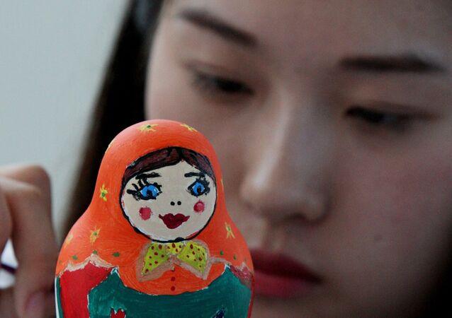 Une étudiante chinoise peint une matriochka. Image d'illustration