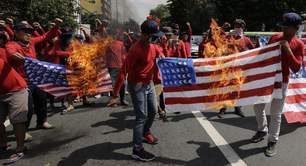 les manifestants brûlent un drapeau américain à Manille