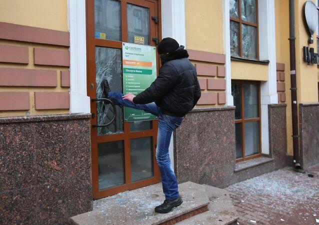 Un extrémiste ukrainien essait de briser une porte d'une succursale de la banque russe Sberbank à Kiev