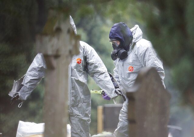 Members of the emergency services help each other to remove their protective suits at the site of the grave of Luidmila Skripal, wife of former Russian inteligence officer Sergei Skripal, at London Road Cemetery in Salisbury, Britain, March 10, 2018.