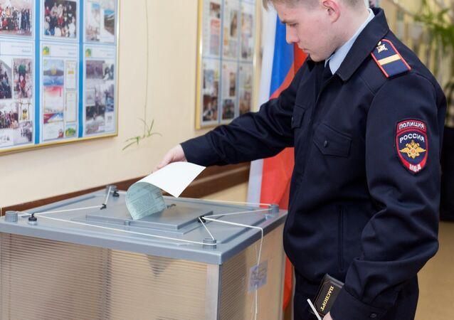 Un policier dépose son bulletin de vote dans l'urne dans le bureau de vote de Petropavlovsk-Kamtchatski.