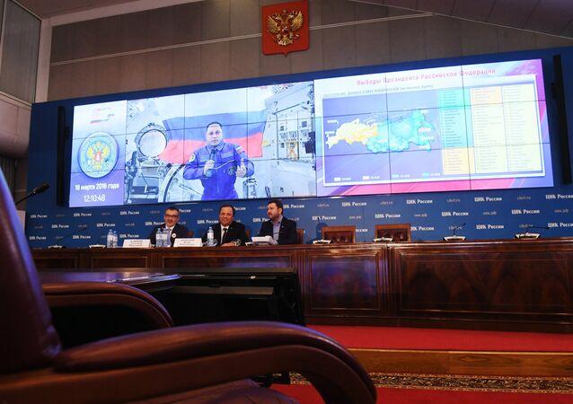 Une session de communication avec l'équipage de la Station spatiale internationale  dans le centre d'information de la Commission électorale centrale russe lors des élections présidentielles en Russie. Sur l'écran: le cosmonaute de Roskosmos Anton Shkaplerov.