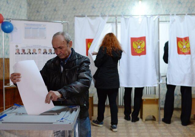 L'homme fait glisser son bulletin de vote dans l'urne en Crimée