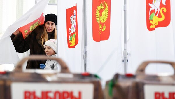 A woman with a child during the voting at the Russian presidential elections at polling station No. 13-06 in Moscow - Sputnik France