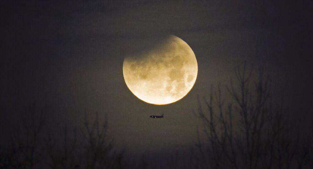 Un avion et la Lune au second plan