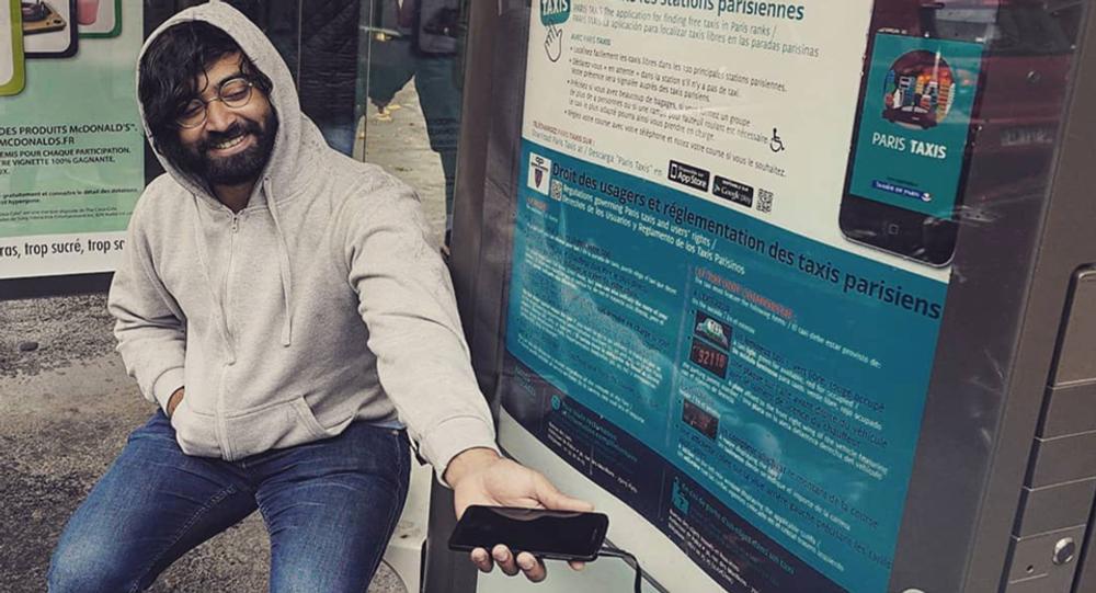 Raj charge son portable à un arrêt de bus