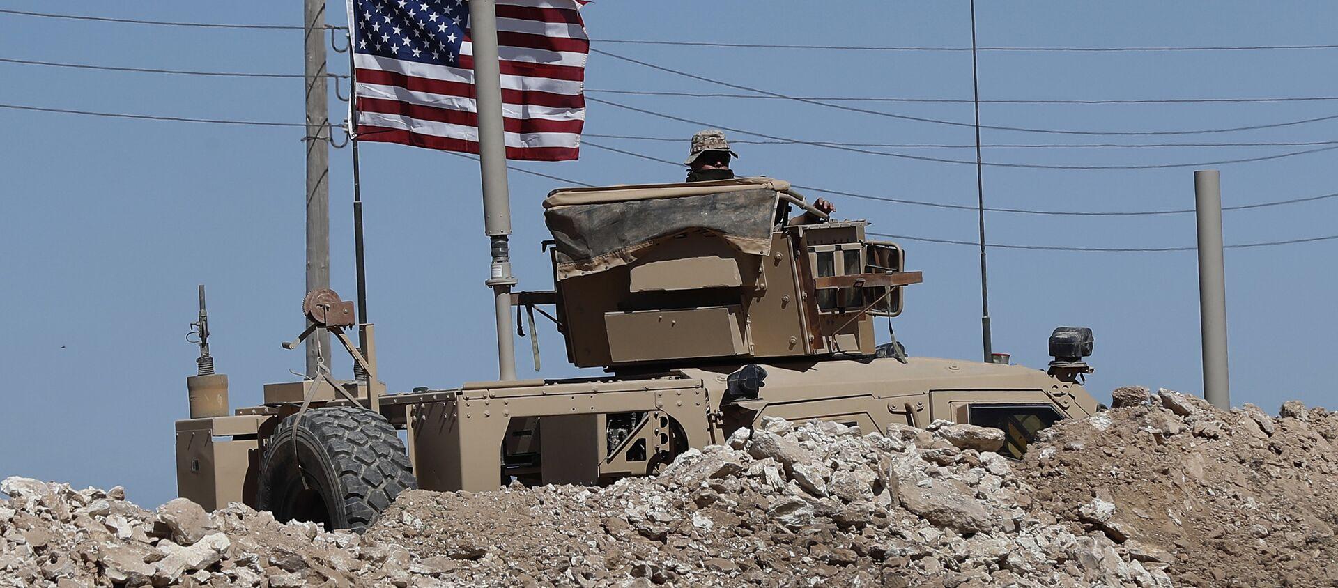 Un soldat américain est assis sur un véhicule blindé derrière une barrière de sable à une position nouvellement installée près de la ligne de front tendue entre le Conseil militaire syrien de Manbij soutenu par les États-Unis et les combattants soutenus par la Turquie, à Manbij, dans le nord de la Syrie, le mercredi 4 avril 2018 - Sputnik France, 1920, 11.02.2021