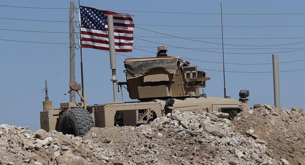Un soldat américain est assis sur un véhicule blindé derrière une barrière de sable à une position nouvellement installée près de la ligne de front tendue entre le Conseil militaire syrien de Manbij soutenu par les États-Unis et les combattants soutenus par la Turquie, à Manbij, dans le nord de la Syrie, le mercredi 4 avril 2018